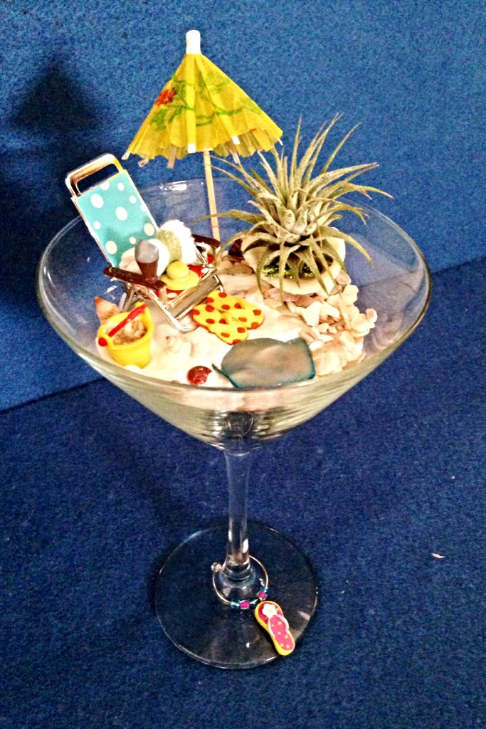 Day At The Beach In A Martini Glass   Beach scene with air plant surrounded by a mini beach chair and towel, umbrella, bucket of seashells and tiny flip-flops. Flip-flop charm at the base of the glass.   Jody's Boutique Gardens - Bellevue, NE