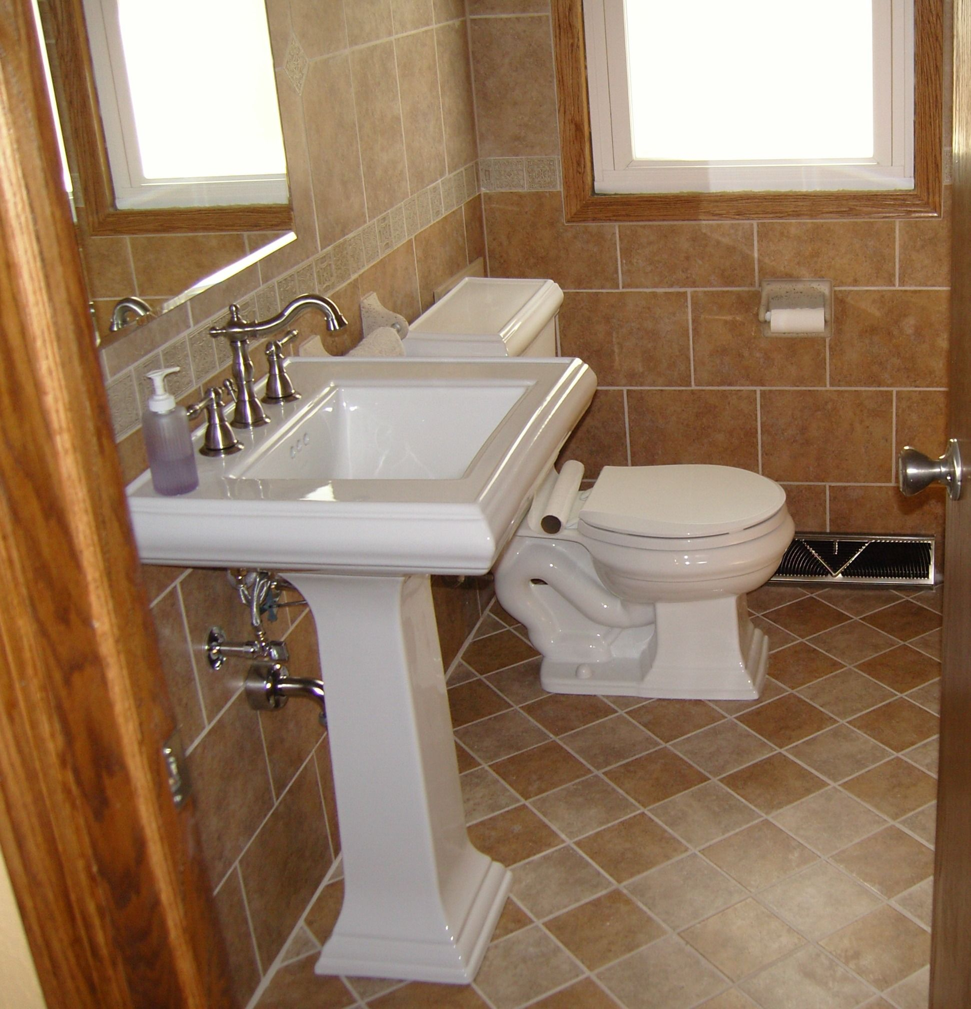 great white single pedestal sink on brown mosaic marble bathroom