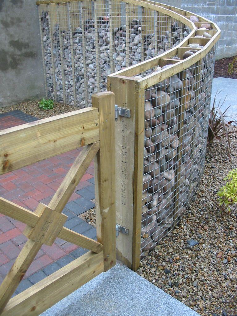einfacher Zaun aus Holz Gitter und viel Steinen