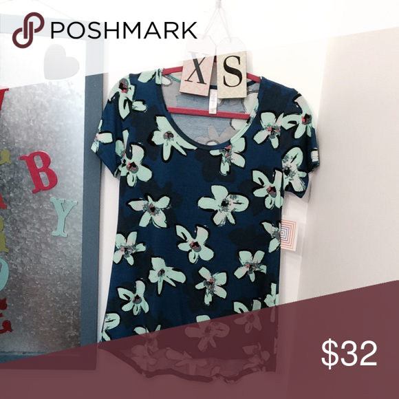 Classic T Tee Shirt by LuLaroe This floral Classic T is sure to become a wardrobe staple as the perfect compliment to all your LuLaRoe skirts and leggings. The Classic T is made from comfortable spun polyester jersey and is short sleeved with a high round neck line. It pairs well with leggings as the back is slightly longer to flatter bodies of all shapes and sizes. This tee runs 1 size larger than true fit. LuLaRoe Tops Tees - Short Sleeve