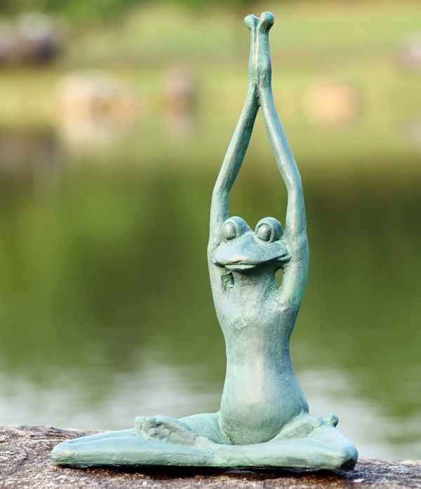 Stretching Yoga Frog Garden Sculpture -Cast aluminum stylized Frog sculpture sitting in a classic Yoga position with crossed legs while stretching its arms high above its head with palms pressed together. The Yoga Frog has been treated with a durable verde green bronze patina and is suitable for outdoor environments.