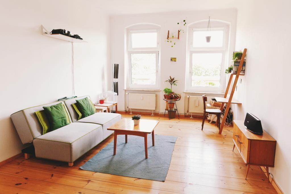 Altbauwohnzimmer mit Holzdielenboden, hohen Fenstern und schöner ...