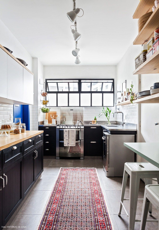 Cozinha com ar industrial tem subway tiles, prateleiras de pinus e armários pretos.
