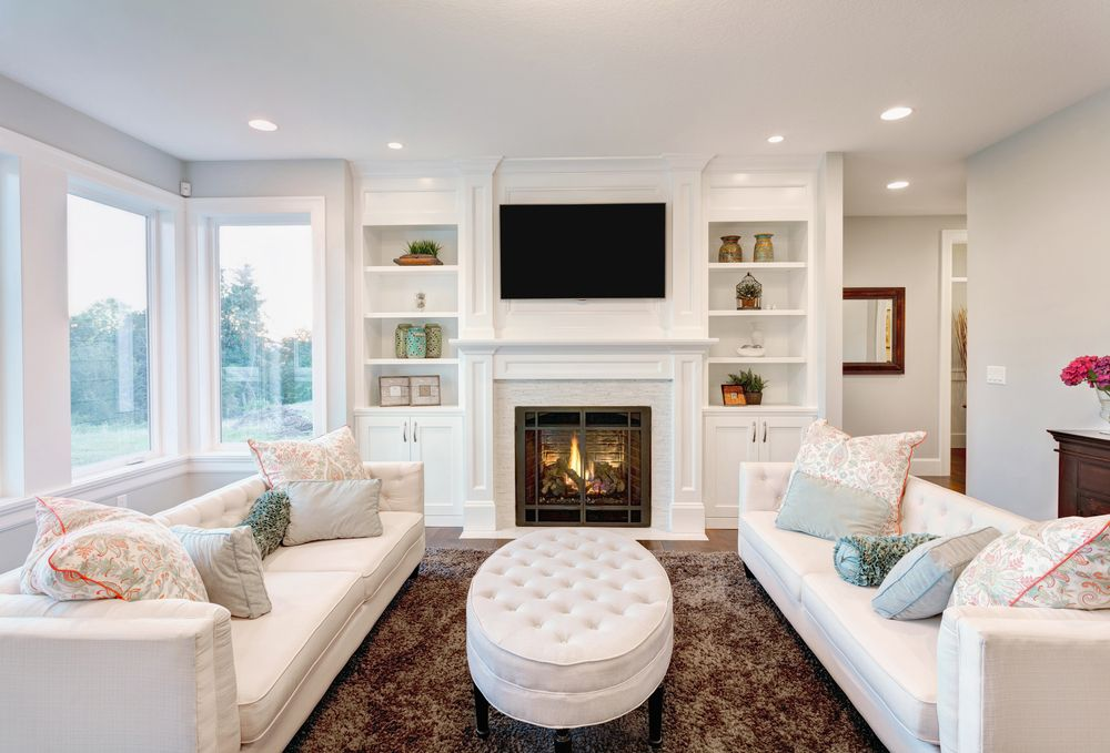 All White Family Room With Built In Shelving Around Fireplace Two Sofas