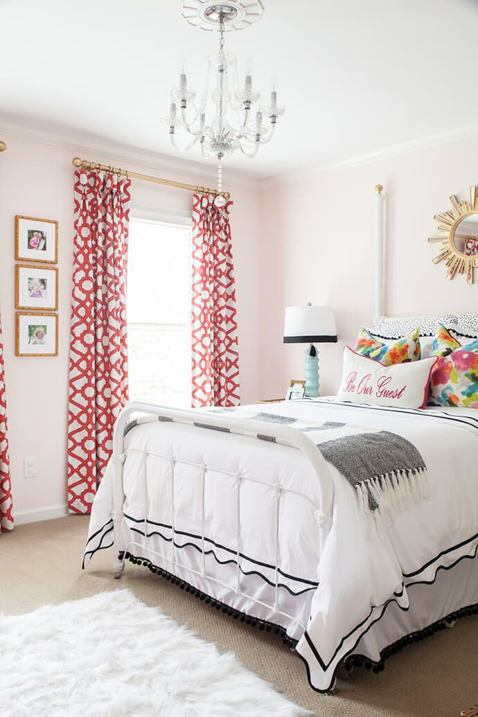 Feminine Bedroom With Pink Walls A White Metal Headboard Printed Curtains And Chandelier