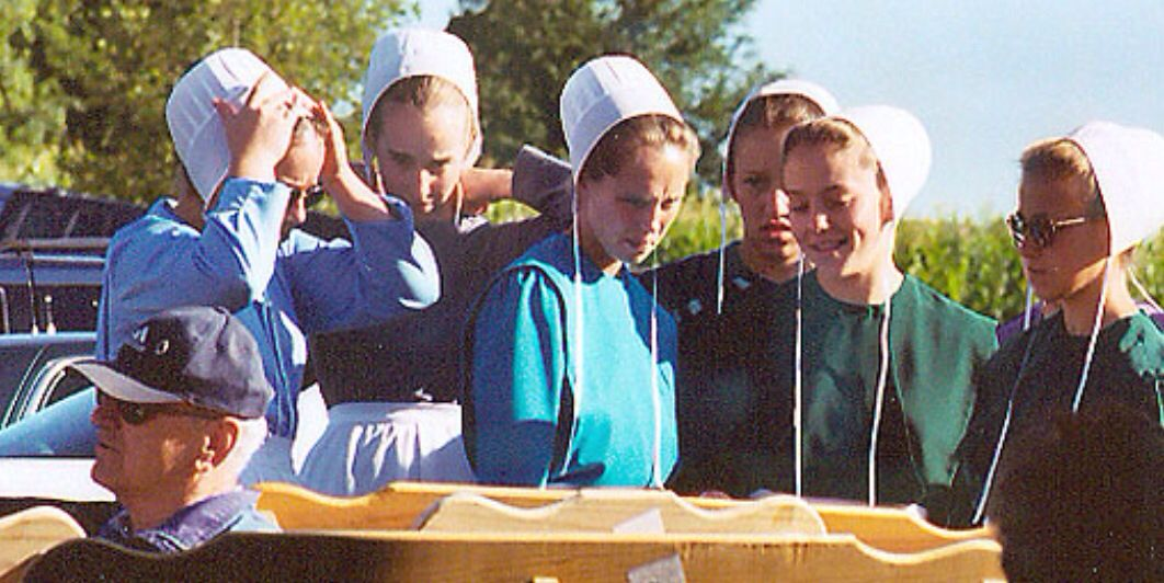 Amish girls looking at furniture for sale. Amish family