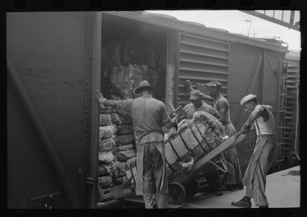 Unloading bale of cotton from freight car. Cotton compress