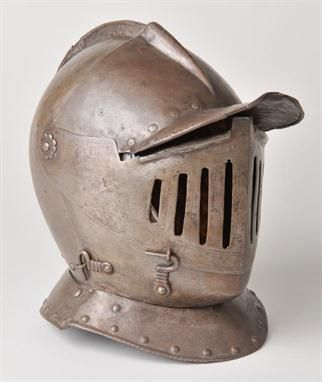 Cuirassiers helmet. An early 17th century Cuirassiers steel helmet probably English c.1640, the rounded skull with raised comb, plume holder at the rear, pointed visor and upper and lower bevors with frontline piece pierced with graduated bars for breathing holes, with locking catches on the right, main edge bordered with engraved lines, retaining much of the original lining, 30cm high (1)