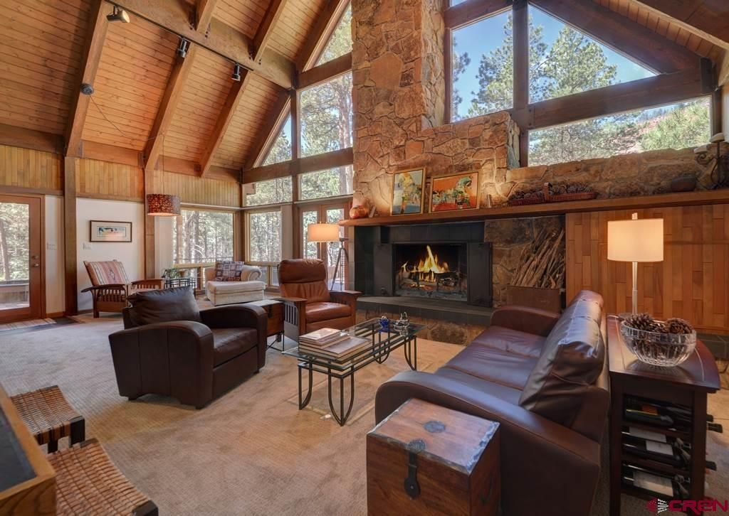 Modern Rustic Living Room. Cathedral ceiling with exposed beams and that wall of wood and windows.