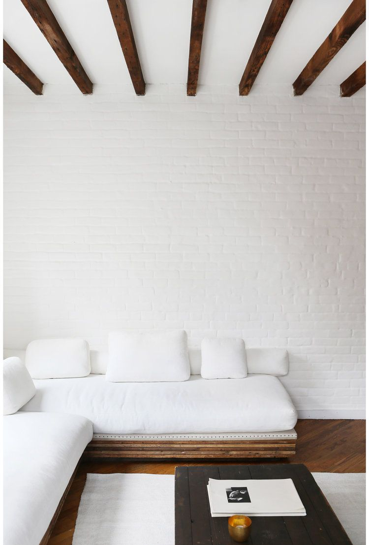 White brick wall wood beam ceiling low platform sofa sectional living room