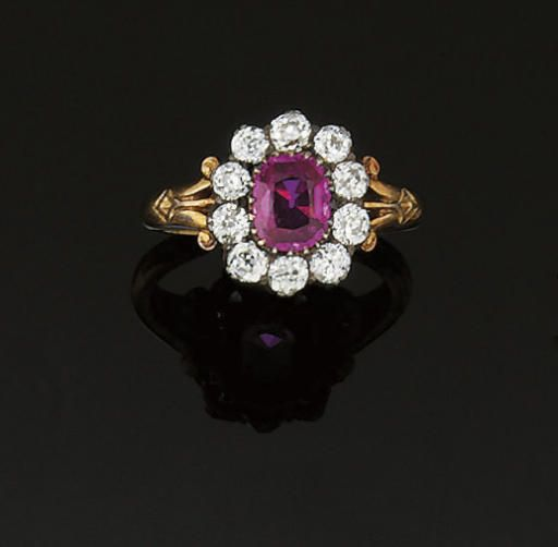 A LATE 19TH CENTURY RUBY AND DIAMOND CLUSTER RING  The central cushion shaped ruby to an old brilliant-cut diamond surround with openwork scroll shoulders, circa 1890