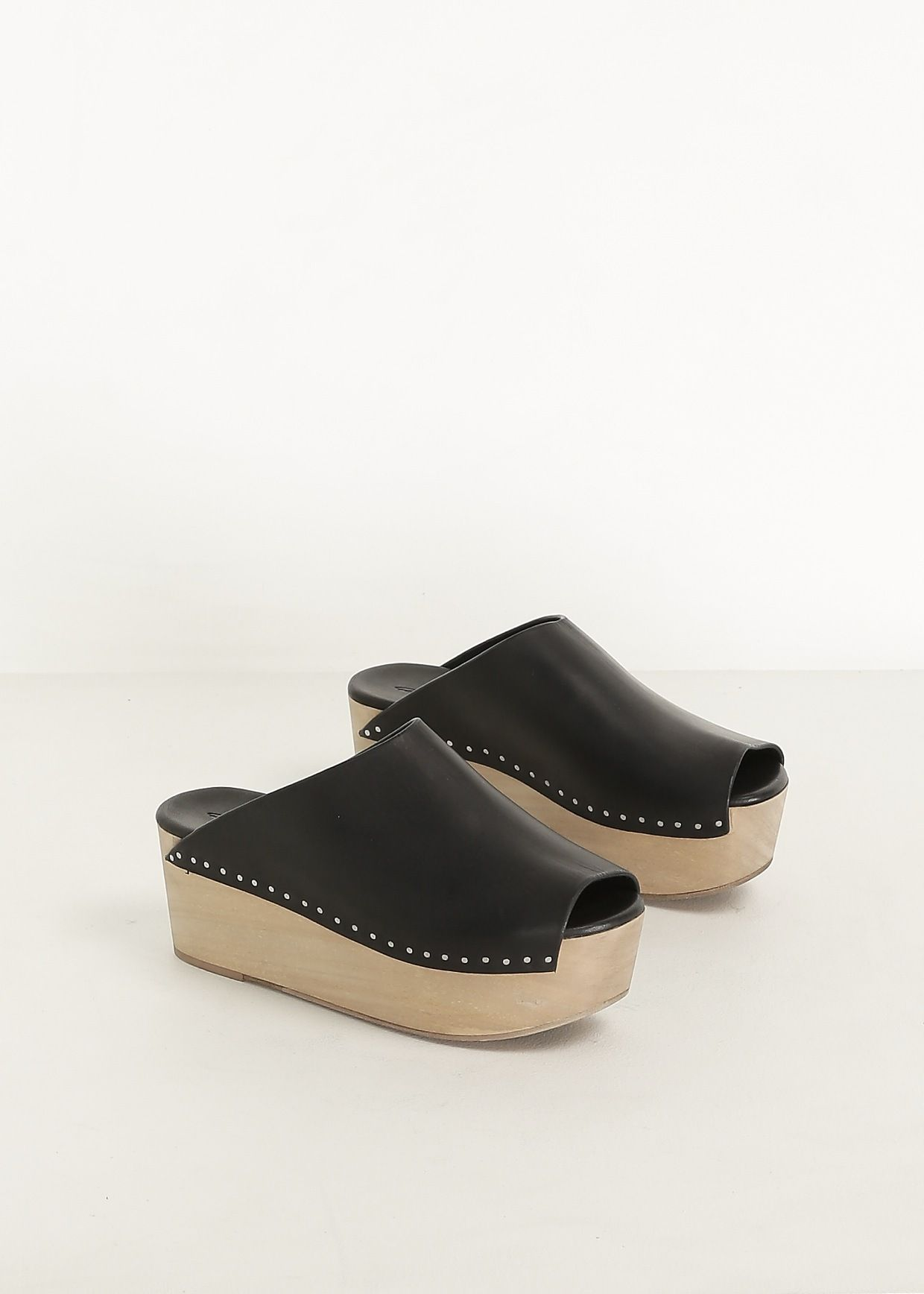 d6bda76edec Leather open-back clog with wooden platform. Peep-toe with exposed silver  nailheads along wedge. Treaded rubber sole