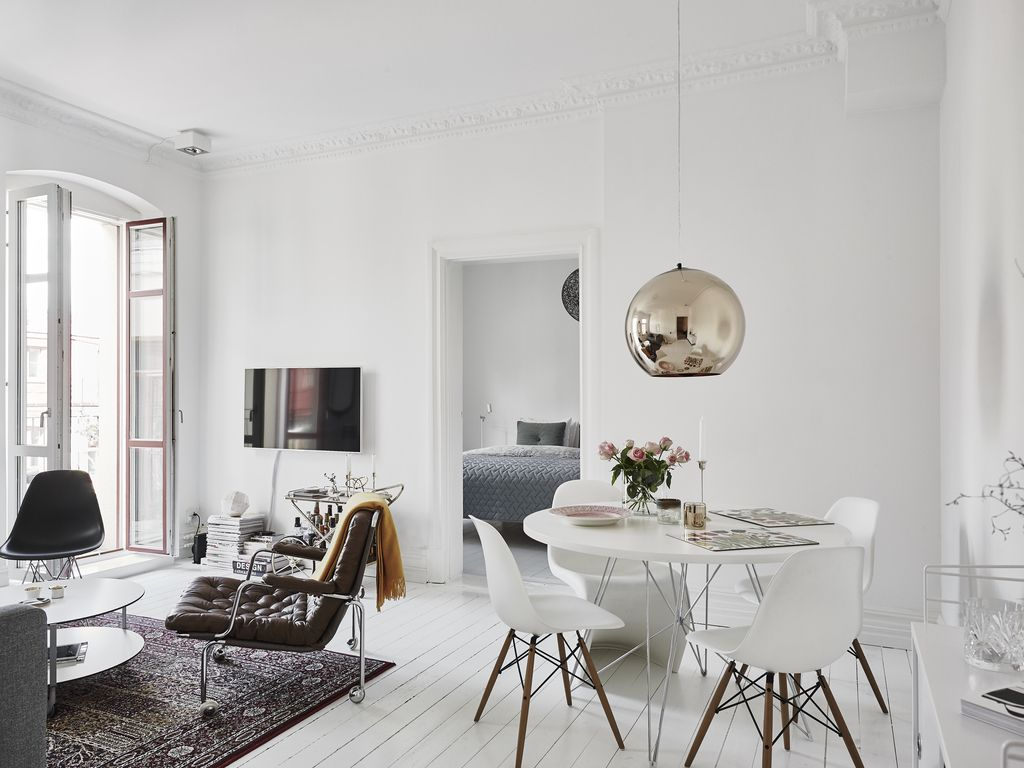 white living room dining table Eames chairs gold pendant lamp large double doors armchair nordic design