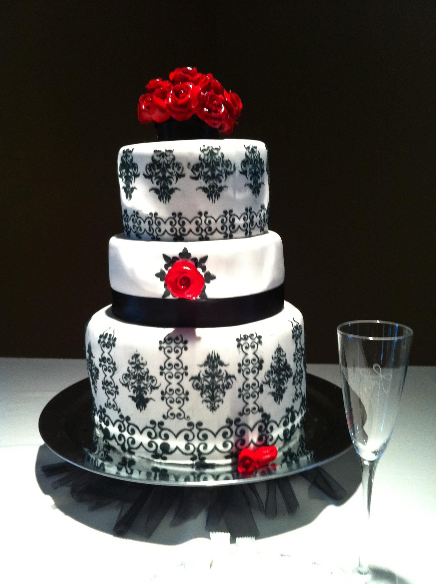 Fondant covered wedding cake hand stenciled with buttercream roses