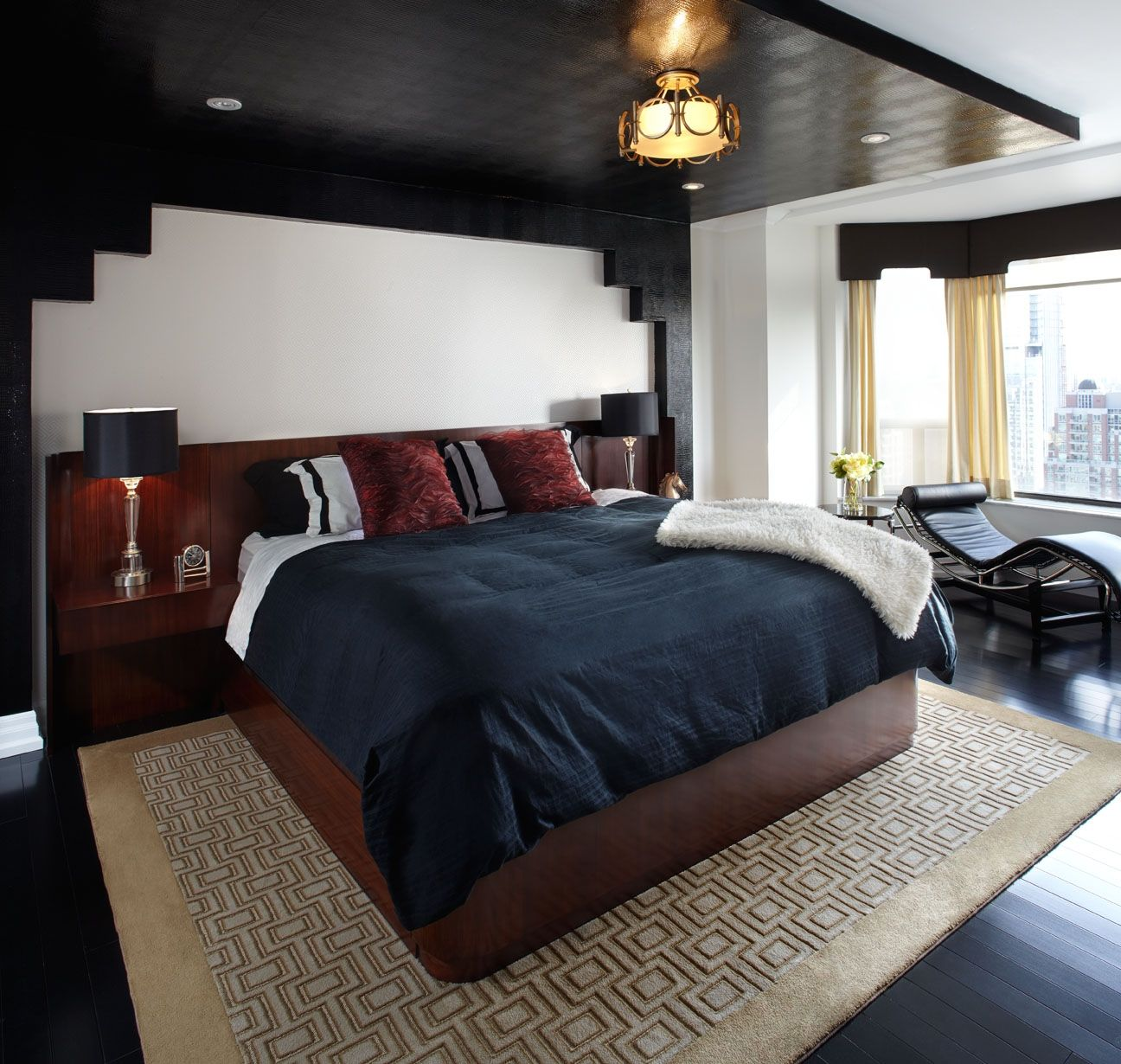 Masculine bedroom with black ceiling, navy bedspread and built-in wood  headboard - LUX
