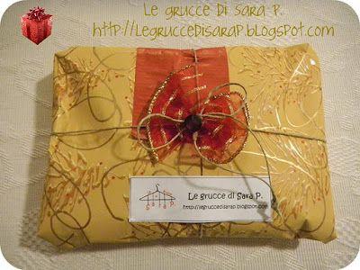 Pacco regalo con carta dorata, spago, cartoncino rosso e una perla marrone
