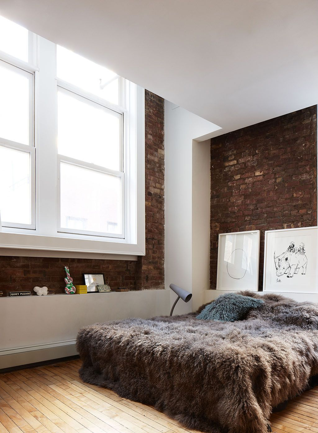 Bedroom with exposed brick and large windows