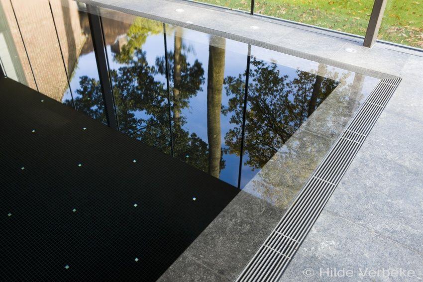 Binnenzwembad overloopzwembad bekleed met zwarte mozaïek de