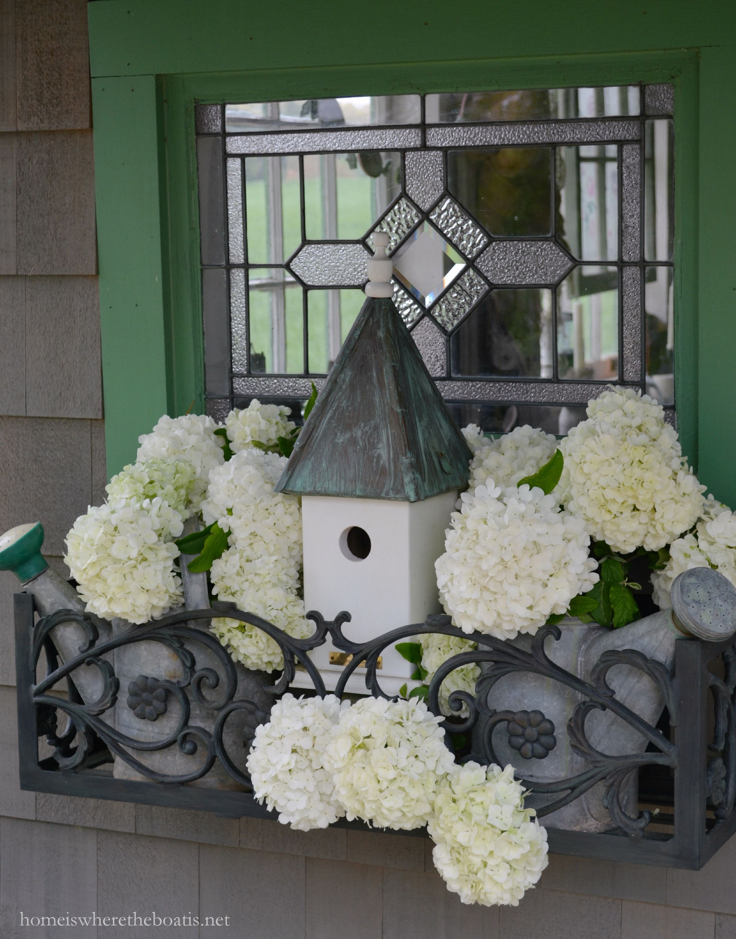 Potting Shed window box with watering cans, bird house and snowball viburnum | homeiswheretheboatis.net #spring #pottingshed #garden