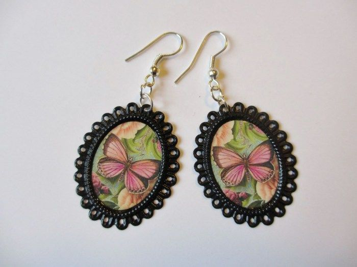 Earrings made of ornate oval-shaped frames and pictures of butterflies. Minka / www.madeby.fi