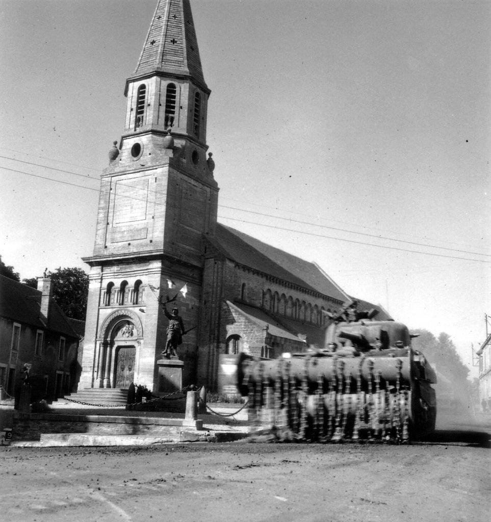 """Le 15 juin 1944, devant l'église Saint Martin de Creully, un char britannique Crab """"fails"""" du 2nd County of London Yeomanry (Westminster Dragoons) de la 30th Armoured Brigade de la 79th Armoured Division du Major-General Sir Percy Cleghorn Stanley Hobart, passe à côté d'un Monument aux morts.  Voir à gauche du char l'insigne de la division et l'unit number : 53, voir ici :  www.flickr.com/photos/mlq/7041515055/in/photostream  Il représente un soldat de la première guerre mondiale tenant dans…"""