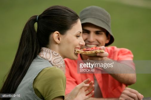 Foto de stock : Young man lets his girlfriend bite from a slice of bread with salami, selective focus