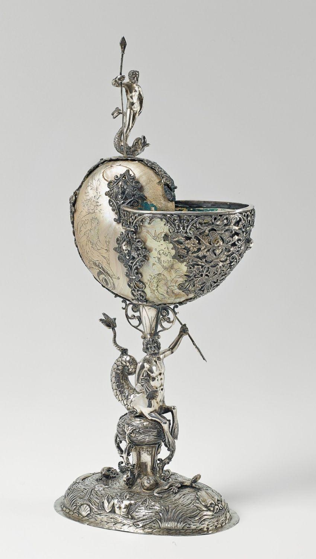 NAUTILUSPOKAL DES HISTORISMUS Silber, getrieben, gegossen und ziseliert. Ovaler, aufgewölbter Fuß mit getriebenen und ziselierten Delphinen, Nereiden und Echsen; ein Tritone mit Horn und Dreizack als Schaftfigur. Der große Nautilus mit fein graviertem Dekor, von drei Silberspangen gehalten; ein Neptun mit Delphin als Bekrönung. Phantasiemarken. Der Nautilus mit restaurierten Sprüngen; innen blau gefasst. H 42 cm, Gewicht 937 g. Wohl Hanau, um 1900.