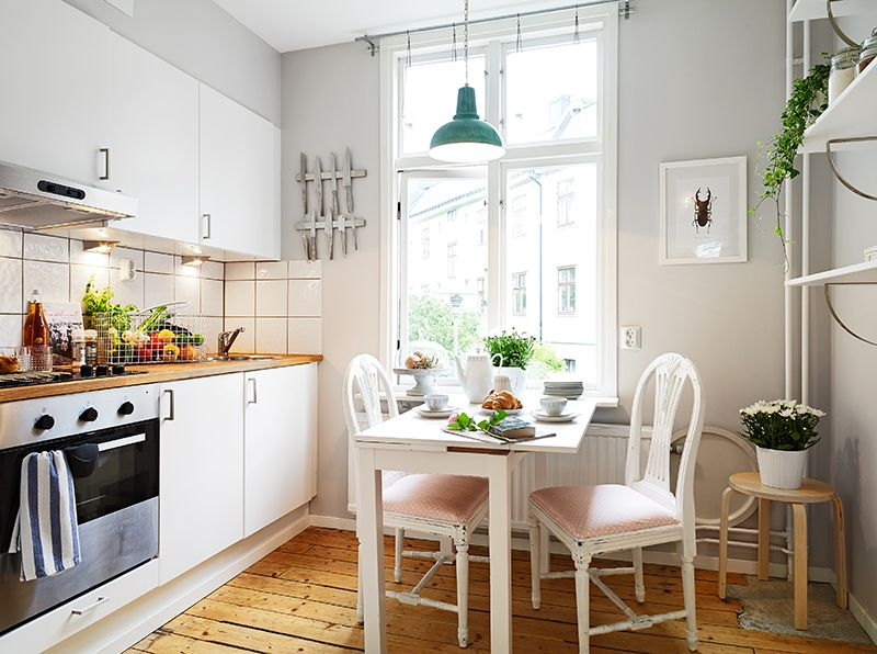 Kitchen - wooden floors, white cabinets and tiles, wooden bench tops, white chairs and breakfast table, houseplants, shelving, ikea.