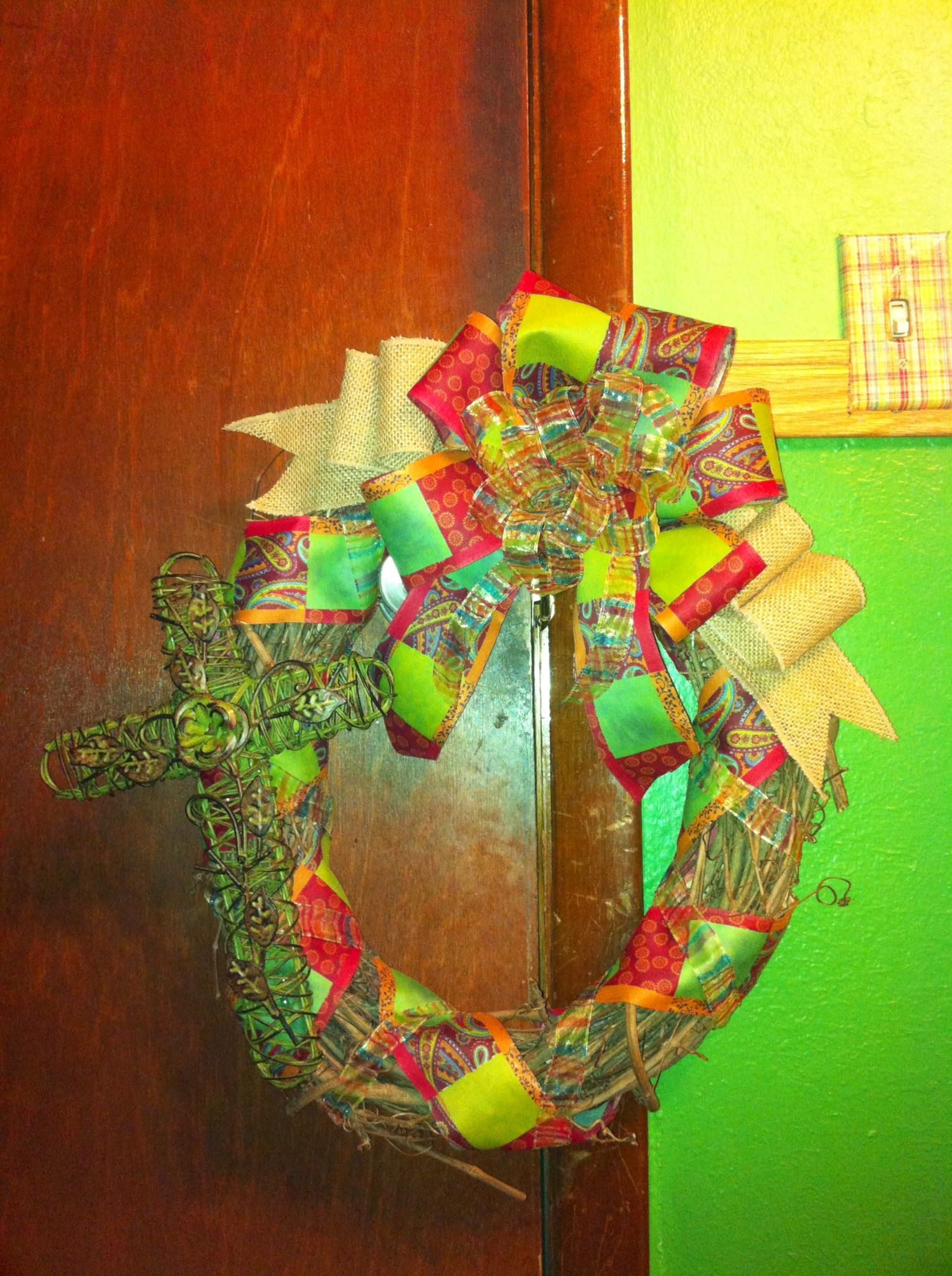 Oval grapevine metal cross wreath adorned with multicolored paisley and burlap bow. All items used purchased at Hobby Lobby. Check out my Facebook page! Search for Crafty Queen Creations!