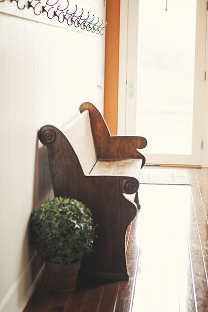 The aged, patinated beauty of this vintage pew glows in a sunlit foyer. Its lines and curves are so striking that very little other ornamentation is needed to complete the space.
