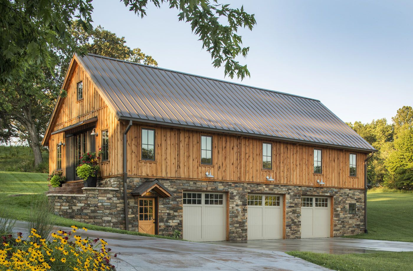Barn home with stone around the 3 car garage sand creek for Wood barn homes
