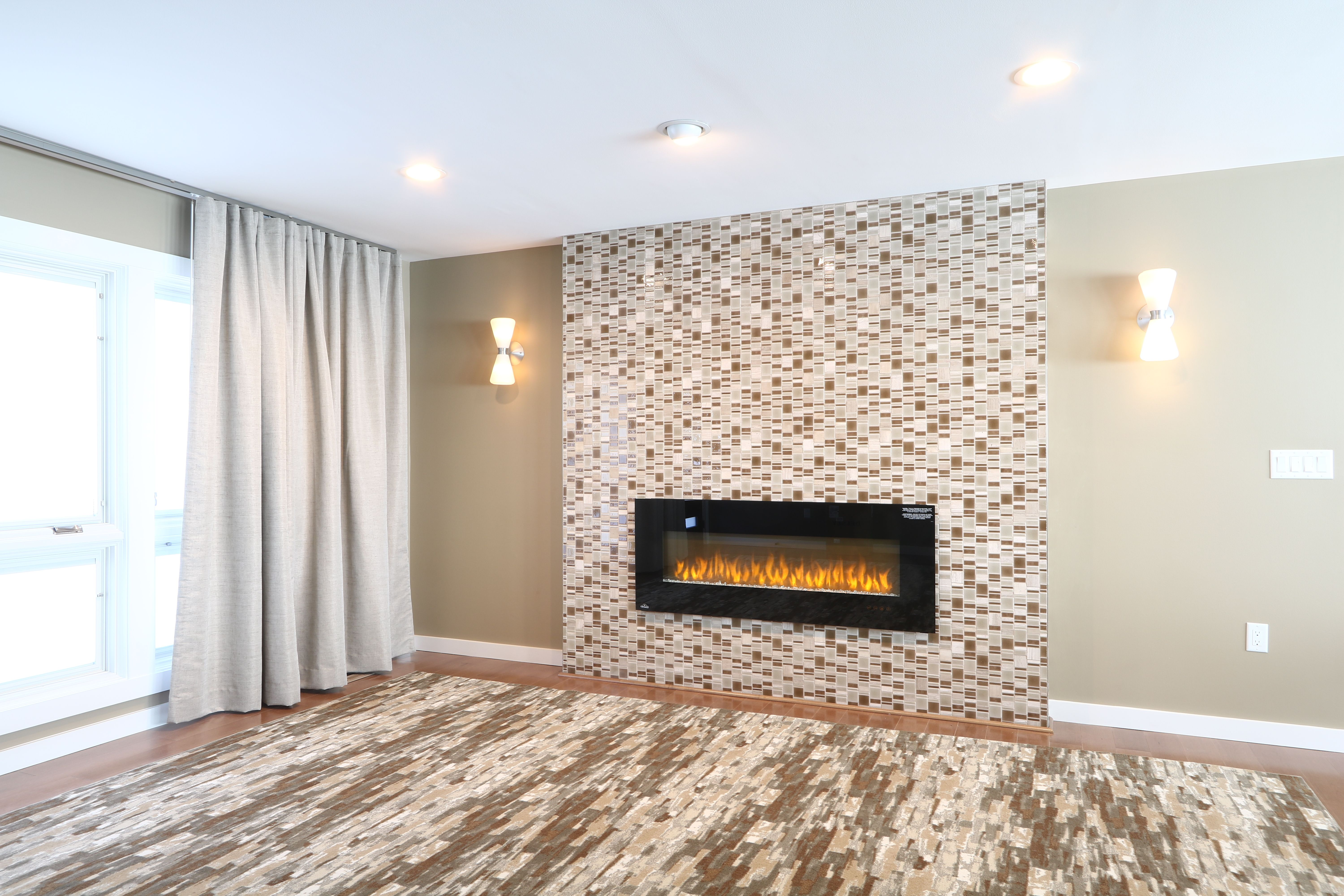 A tiled wall area with electric fireplace, wall sconces, custom ...