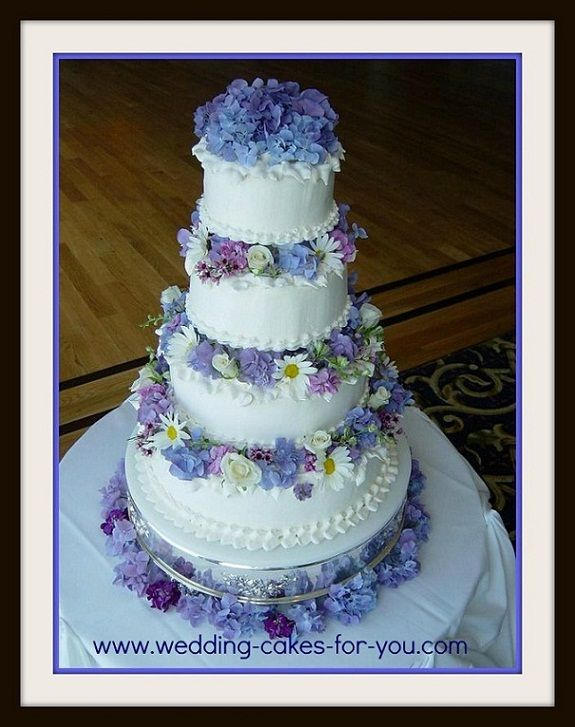 wedding cake with flowers in between layers a four tiered wedding cake with fresh flowers in between 26882