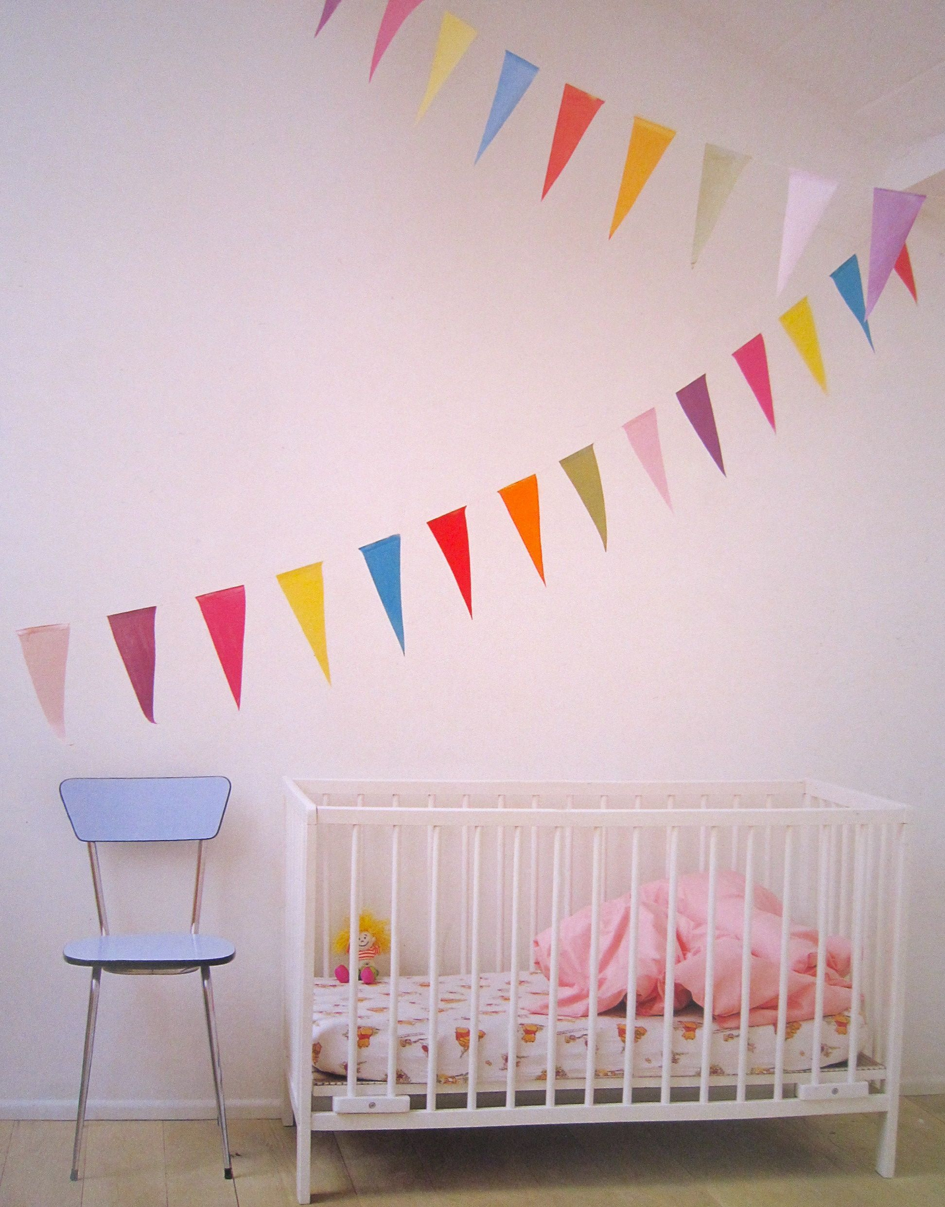 White nursery with rainbow bunting.