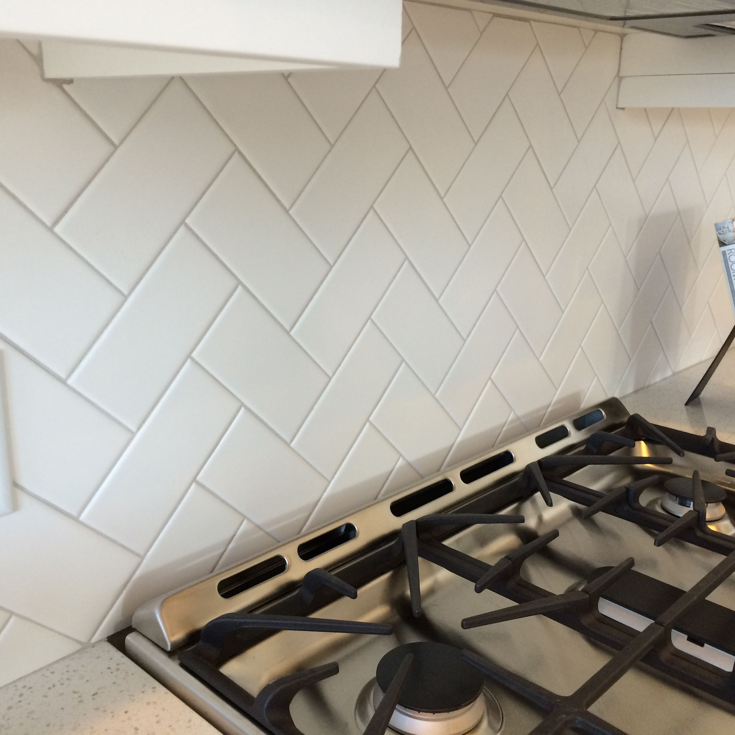 3x6 White Subway Tile In A Herringbone Pattern With Light Gray