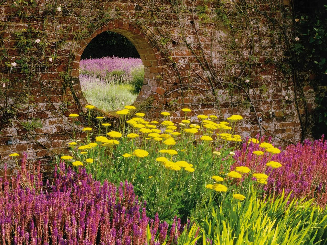 Colorful flower beds provide a welcome contrast against a rustic ...