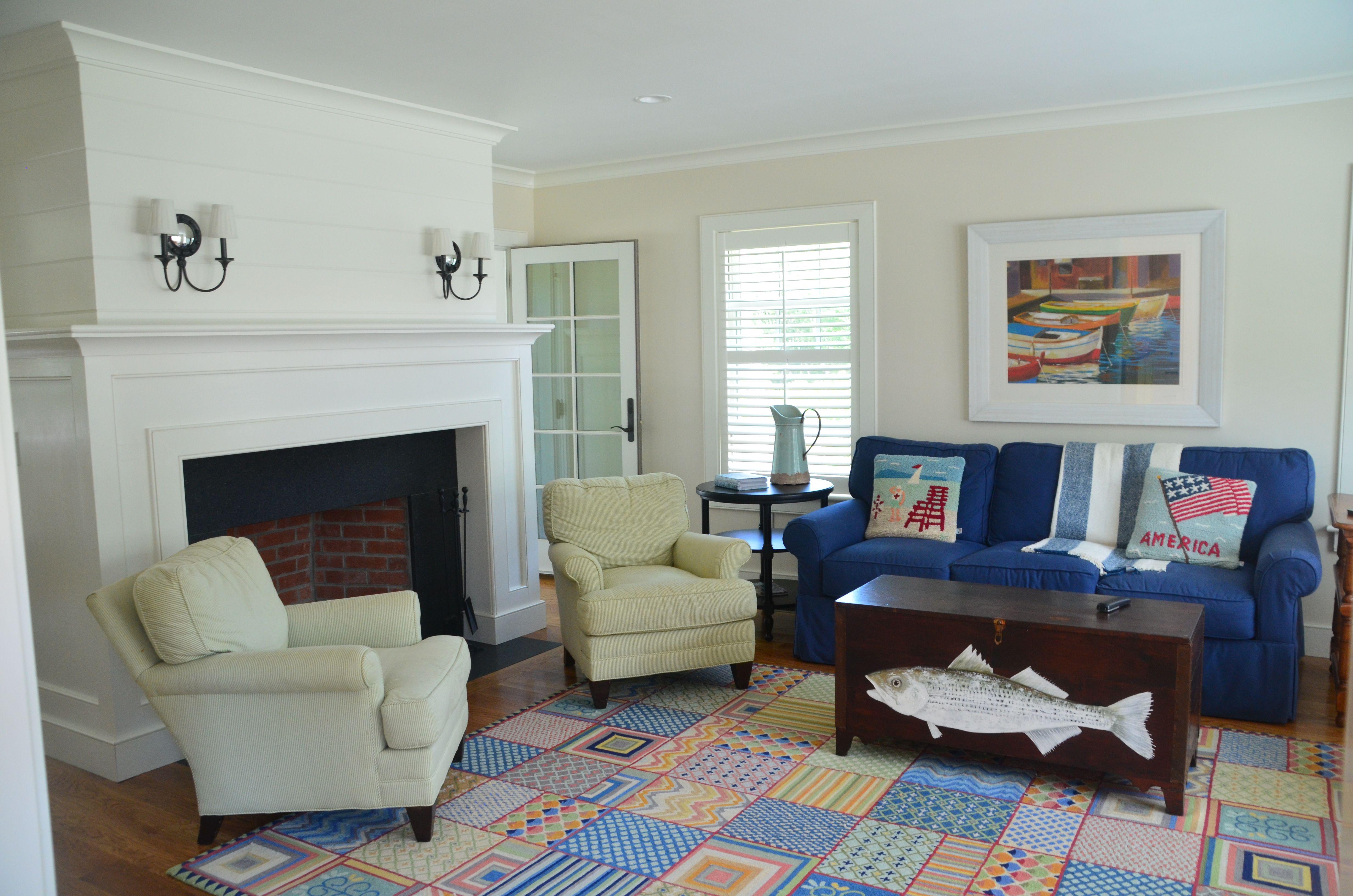 paneled fireplace coastal family room nautical sconces company c rug fish art wide plank. Black Bedroom Furniture Sets. Home Design Ideas