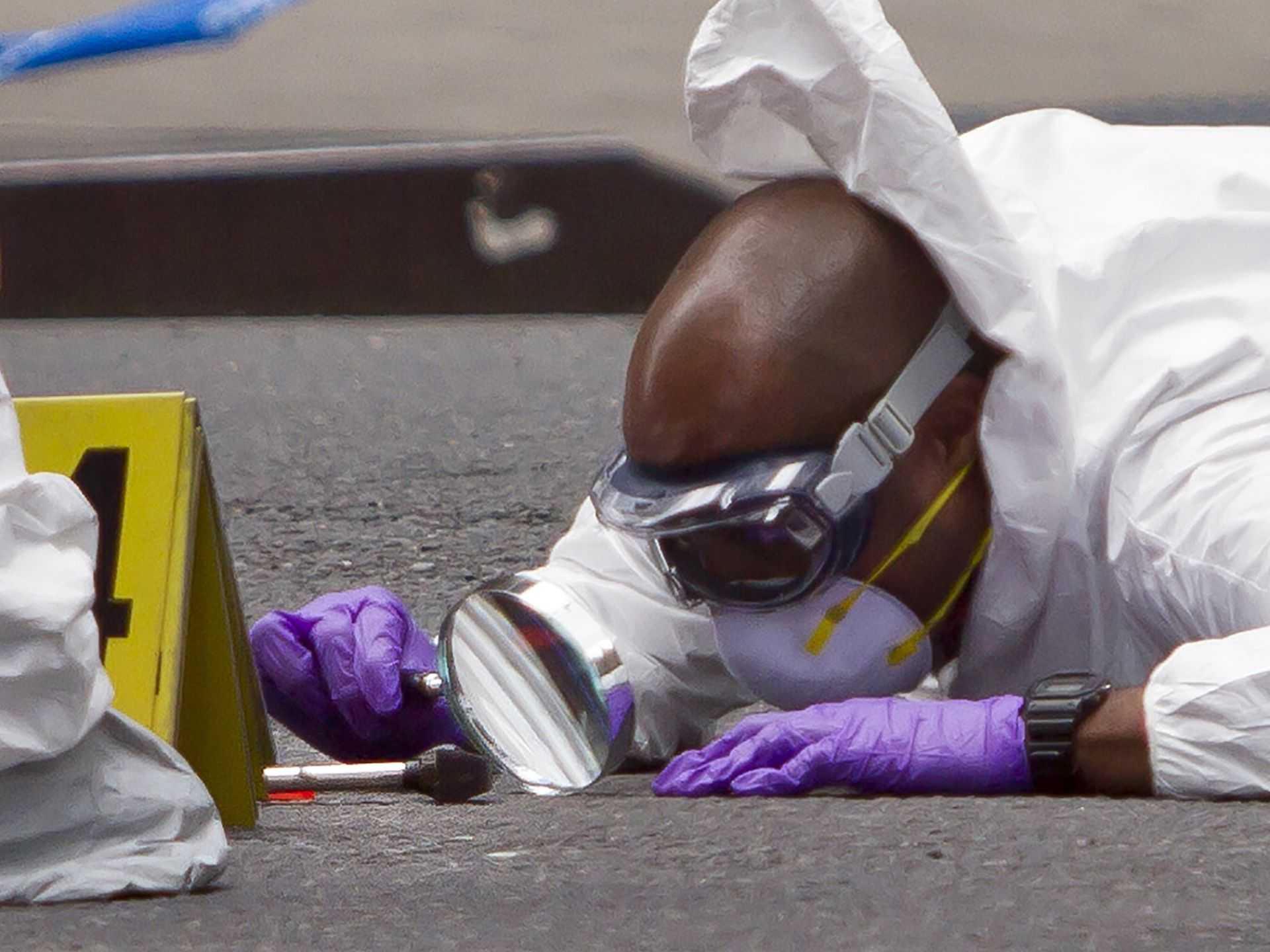 A New York Police Department investigator examines a hammer after a shooting on May 13. A man attacking pedestrians with a hammer was shot by police in Midtown Manhattan.  Bebeto Matthews, AP