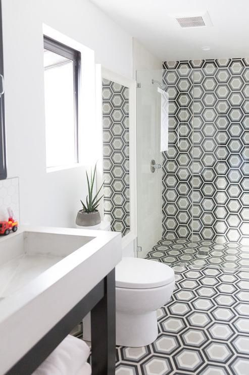 A Black Washstand Finished With A White Porcelain Sink Sits On Black And Gray Hex Floor Geometric Tiles Bathroom Bathroom Floor Tiles Farmhouse Master Bathroom