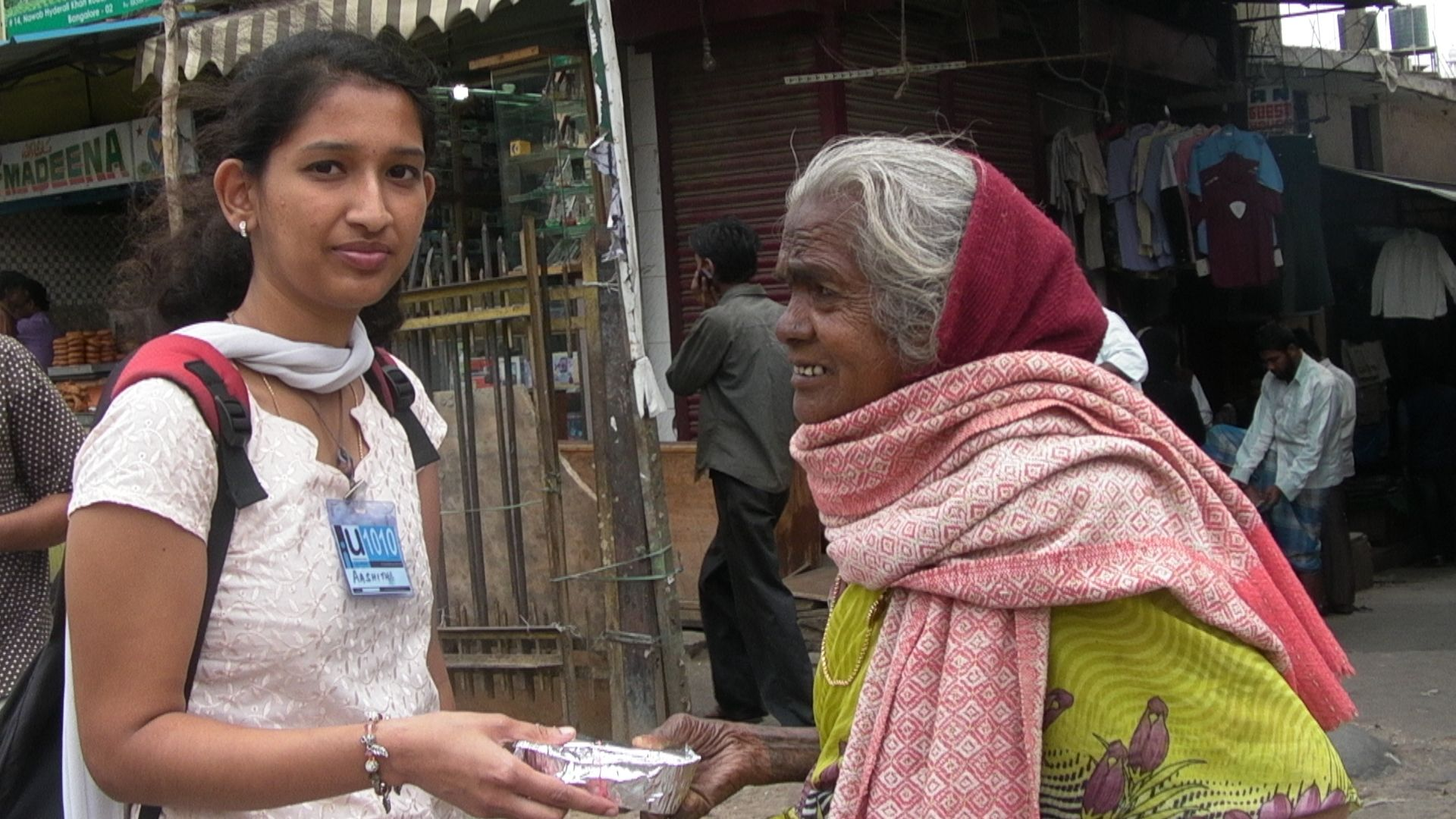 A disabled and a very aged woman gratefully collecting the food