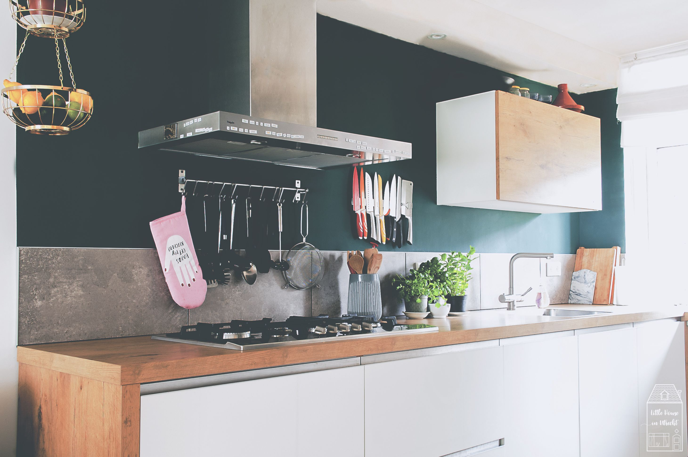 Dark green kitchen wall with white cabinets and wooden ...