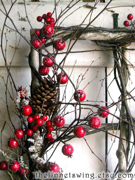 A rustic window frame is constructed of white birch branches, and intertwined with curling twigs. It is adorned with frosted crimson berries and