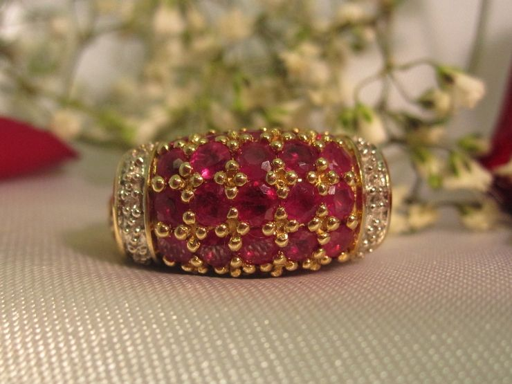 Ruby & diamond cluster ring in 14k yellow gold. This ring is eye-catching and bold and features a row of accent diamonds on both sides. $374