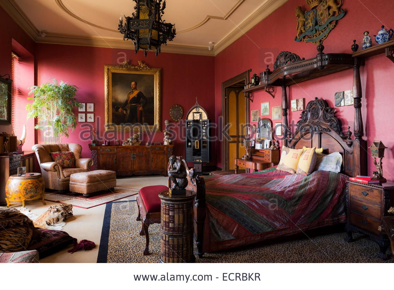 Download this stock image: Ornate carved bed with coronet in large red bedroom with leopard print carpet, wall  mounted coat of arms and antique furniture - ECRBKR from Alamy's library of millions of high resolution stock photos, illustrations and vectors.