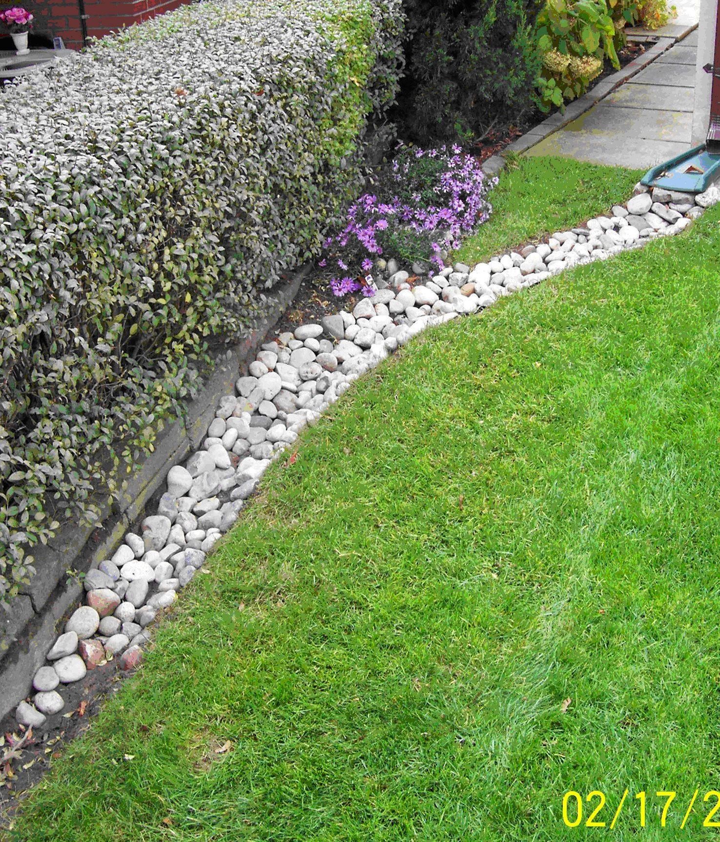 Front yard drain idea river rock landscaping