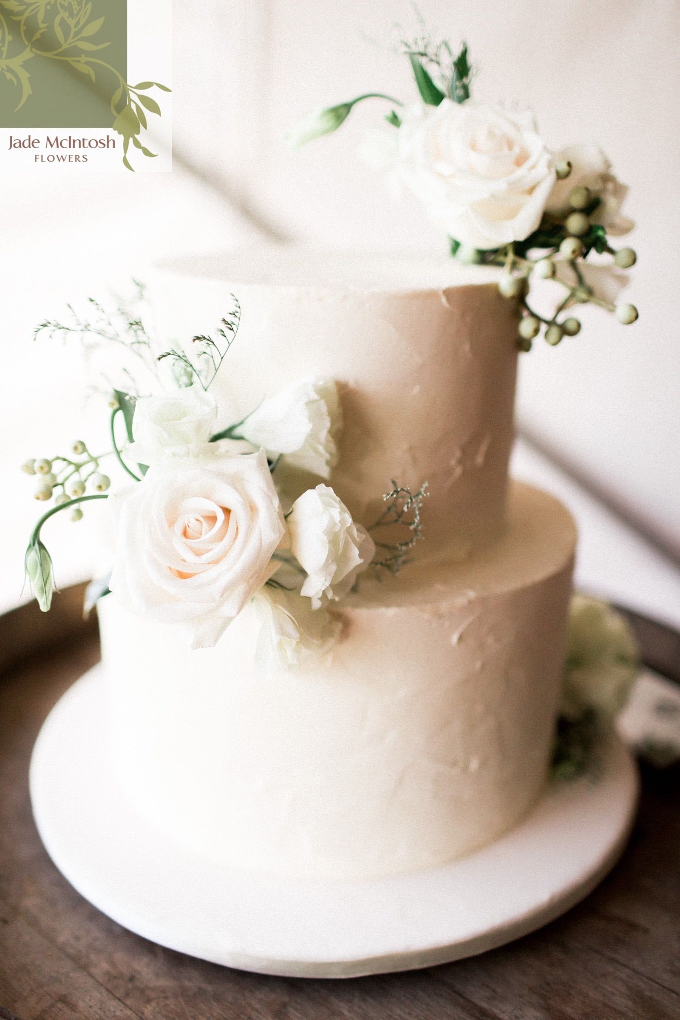A classic two-tier cake finished with posies of open roses ...