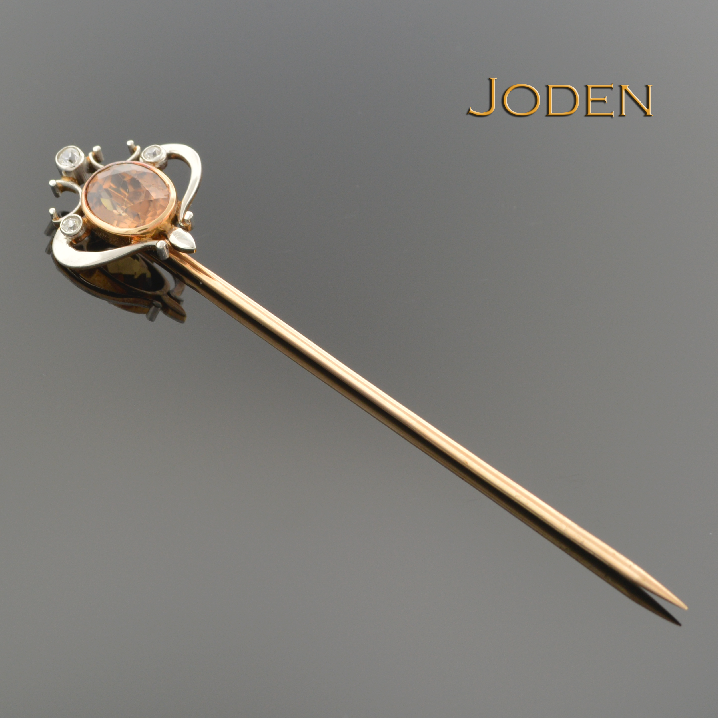 For those who appreciate the delightful design of Edwardian jewelry, this is a noteworthy pin. Stick pins are lovely and understated accessories, adding a touch of sparkle to the lapel. This brooch has a striking two tone design with yellow metal on the back and white on the front. At the top an orange zircon is set and little round diamonds accent the swirling metalwork around it.