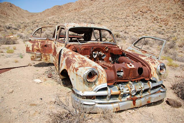 rusty old broken down car that had got bogged in the paddock and
