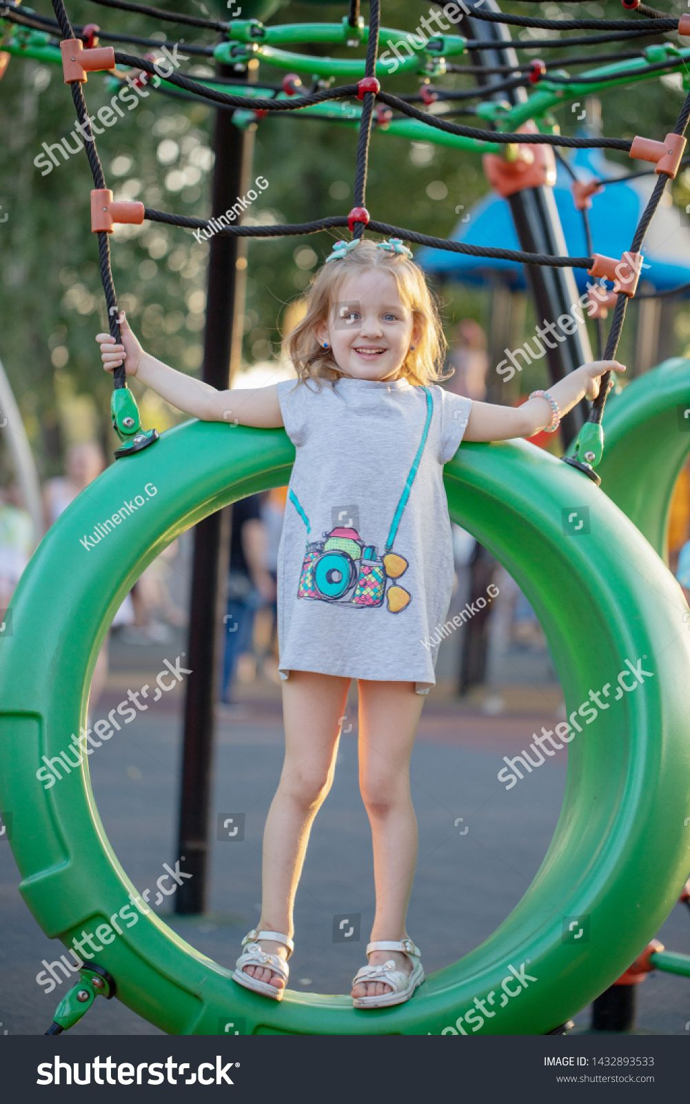 Cute Little Girl Having Fun On A Playground Outdoors In Summer