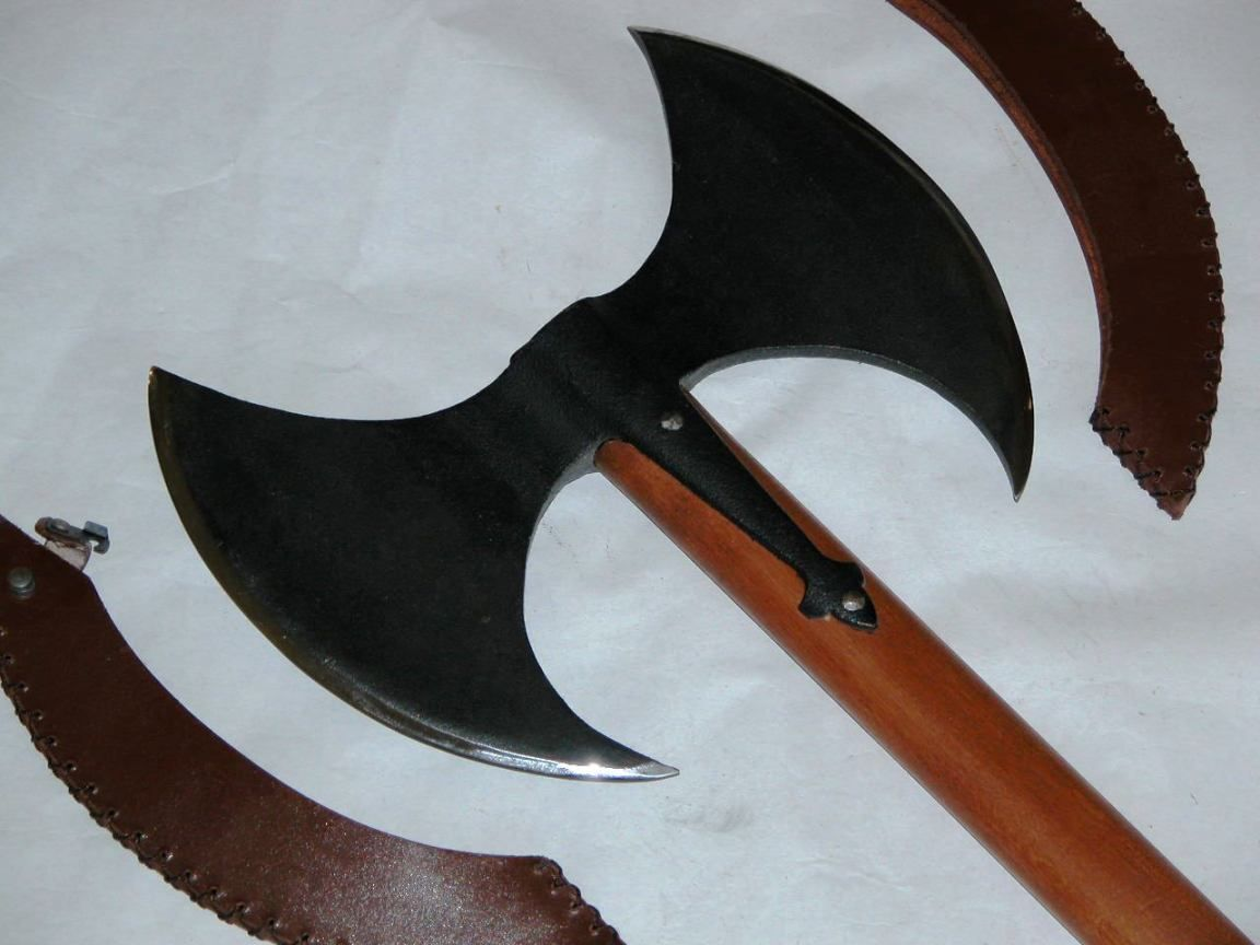 """Paul Chen Hero's Axe.    The legendary double axe has long been associated with heroes and heroics, and the Hero's Axe (PC-1074) perpetuates the legend. Almost 30"""" overall with 10"""" polished edges, fearsome but with graceful lines and studded decoration, this axe is the ultimate combination of form and function. Leather edge covers for the tempered edges are provided for safe portability.   KEY FEATURES: • Double Bladed  • Forged head with tempered edges"""